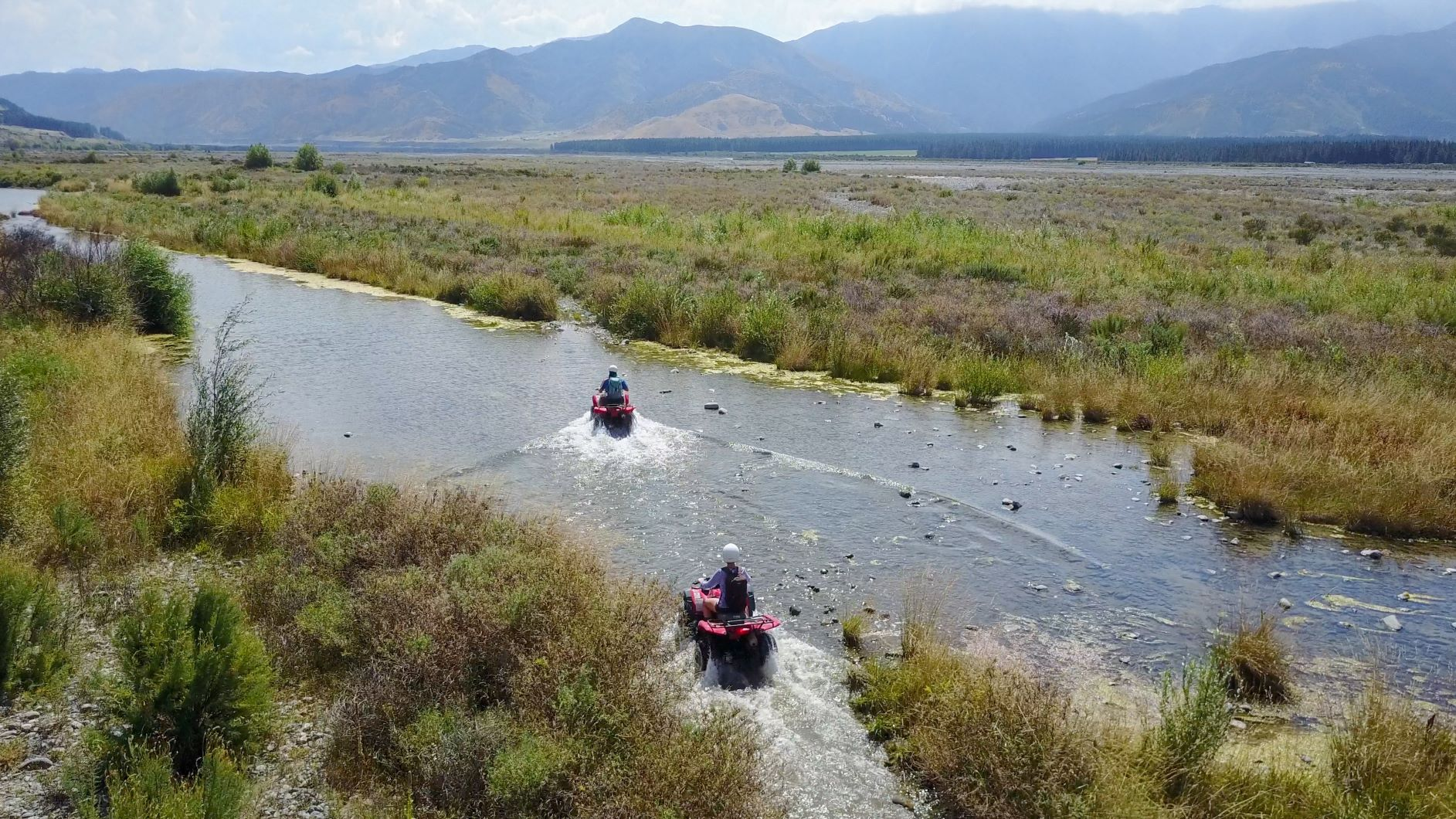 Two people driving through a river on Hanmer Springs Attractions quad bikes